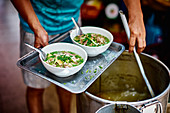 Bowls of noodle soup pho bo being served on a tray