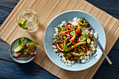 Grünes Gemüsecurry aus dem Wok auf Reis