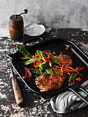 Escalope with colourful vegetables in a grilled pan