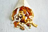 A paper bag of dried fruit, nuts and coconut chips