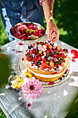 Strawberry sponge cake being decorated with flowers