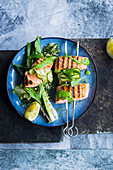 Salmon skewers with wild garlic, courgettes and spring onions