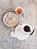 Homemade coasters, a teapot, a teacup and cinnamon buns