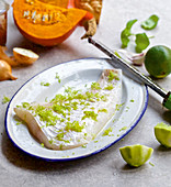 A raw cod fillet topped with lime zest