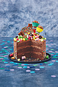 A chocolate buttercream cake with sprinkles, topped with popcorn and sweets