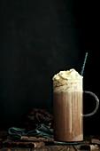 Heiße Schokolade mit Schlagsahne im Henkelglas vor schwarzem Hintergrund