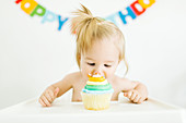 A little girl sitting in a high chair with a muffin for her first birthday