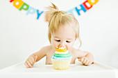 Kleines Mädchen sitzt im Hochstuhl vor Muffin zum ersten Geburtstag