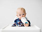 Kleiner Junge sitzt im Hochstuhl und trinkt Milch aus Milchflasche