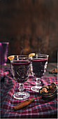Mulled wine with spices and orange peel, served in stemmed glasses