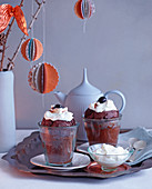 Coconut and chocolate cake in glasses with amarena cherries and cream