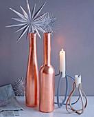 Weihnachtsdeko mit Silbersternen, kupferfarbenen Flaschen und Kerzen