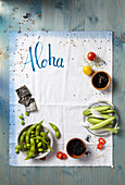 Various Asian ingredients, a tea towel with 'Aloha' written