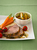 Sliced leg of lamb with garnished vegetables