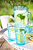 Water with lemon and mint on a garden table