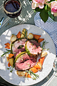 Lamb with a herb crust and vegetables on a summery table outdoors