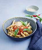 Wholemeal penne pasta with a tomato and courgette sauce and basil