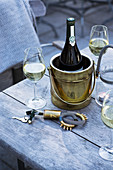 Bottle of white wine in ice bucket and two wine glasses