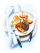 A rosemary lamb cutlet with glazed apple and onion slices