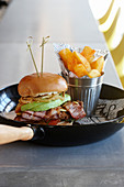 A burger with avocado and bacon, served with french fries in a small metal container