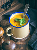 Thick pumpkin soup in a rustic metal cup.