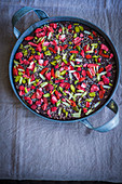 Homemade chocolate bark with goji berries and pistachios in a metal container