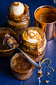 Sticky toffee pudding baked in glass jars with vanilla ice cream and caramel sauce