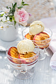 Grilled peaches with vanilla ice cream in dessert bowls on a summer table outside