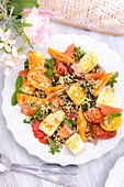 Summer buckwheat salad with tomatoes and halloumi on a table outside