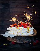 Pavlova with fresh berries, passion fruit sauce and sparklers