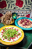 Hummus sharing plate garnished with herbs and pomegranate seeds with crispy flat bread pieces in colourful plates and background