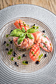 Lobster meat tartare with a pesto and balsamic dressing and tomato garnished with basil on a glass plate