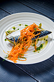 Blue mackerel fish fillet with aubergines and carrots drizzled with olive oil and garnished with dill and herbs on a white plate