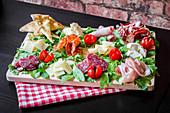 Italienische Wurst-Käse-Platte mit Rucola und Kirschtomaten