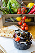 Fresh mussels in a white wine and tomato sauce with red onions and cherry tomatoes in a pot