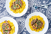 Three portions of osso buco milanese meat on a yellow saffron risotto garnished with fresh chopped parsley
