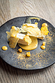 Persimon cheesecake with a persimon puree and crisps on a black plate and light wooden background