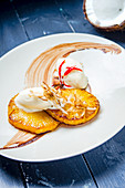 Honey glazed grilled pinapple with coconut sorbet ice cream, essiccated coconut flakes and chilli on a white plate and blue table