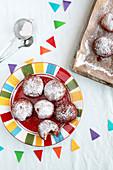 Krapfen mit Marmelade auf Backblech und auf buntem Teller mit Girlande