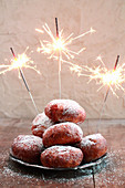 A stake of doughnuts on a plate with burning sparklers