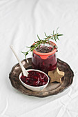 Cranberry sauce in a jar and a dish with rosemary and a wooden star on a silver plate