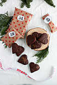 Stuffed gingerbread hearts coated in chocolate next to Advent calendar parcels