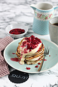 A stack of ricotta pancakes with vanilla yoghurt and raspberries