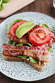 An open BLT sandwich with avocado