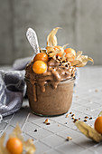 A frozen banana smoothie with cocoa, physalis and almonds
