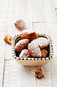 A bowl of homemade, deep-fried pastries with icing sugar
