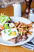 Beef rump steak topped with fried egg and chives herbs served with golden chips and fresh salad on a white plate on a wooden table