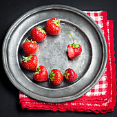 Fresh strawberries arranged circularly on a dark pewter metallic plate with a red and white napkin on a black background