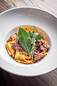 Fresh homemade pappardelle tagliatelle pasta with slow cooked game ragu in red wine and bay leaves garnished with thyme