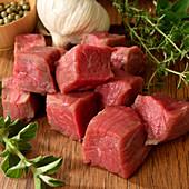 Rohe Rindfleischwürfel, Knoblauch und Kräuter auf Holzbrett